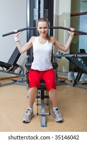 Girl is engaged on a training apparatus in gym