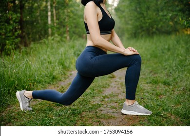 The girl is engaged in outdoor sports in the green forest, exercises with stretching her legs. Close up. The concept of a healthy lifestyle