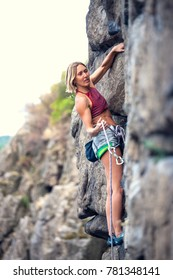 The girl is engaged in sports rock-climbing. The climber climbs the rock. Outdoor activities.