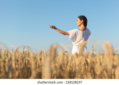 girl enjoy with sunshine in wheat field. Young  woman in white dress in wheat field