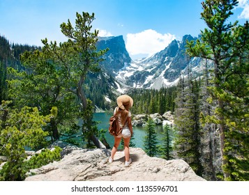Girl enjoying  beautiful scenery on hiking trip. Early summer landscape with lake  and snow covered mountains.  Dream Lake, Rocky Mountains National Park, Colorado, USA.