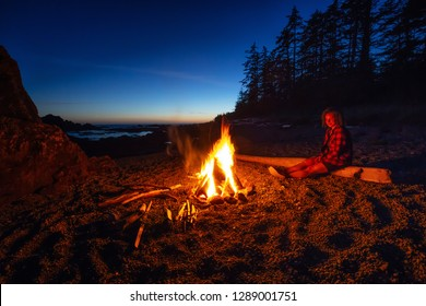 Girl enjoying a camp fire on the beach during a vibrant summer sunset. Taken in Northern Vancouver Island Ocean Coast, BC, Canada.