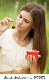 Girl enjoying cherries in the park