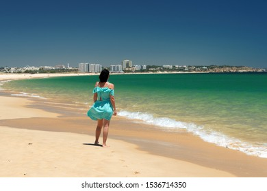 Girl is enjoying the extensive dunes of Alvor Poente beach with its beautiful green water color and golden sand. Vacation in Algarve, Portugal.