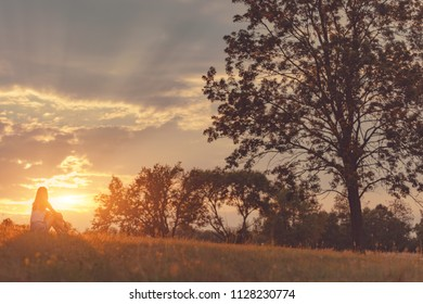 Girl enjoying in the meadow at golden sunset time.