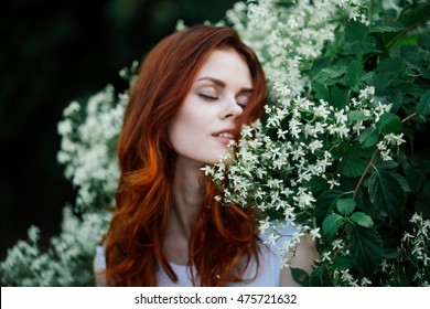 girl enjoying the nature and the smell of white flowers . Harmony between man and nature . Closed eyes