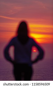 Girl enjoying ocean sunset / sunrise from a high cliff above the water.