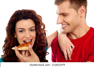 Girl enjoying pizza piece shared by her boyfriend. Great love couple