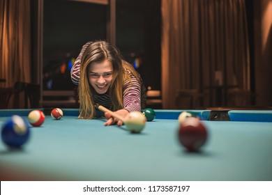 Girl enjoying playing pool at nightout. Great billiards games.