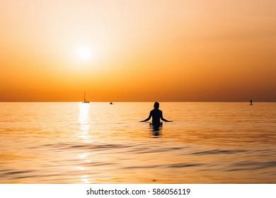 Girl enjoying the sundown in the very calm meridian sea in Tel Aviv, Israel