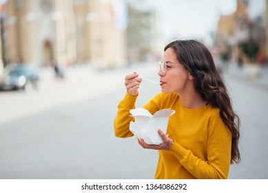 Girl enjoying take away food in the street.