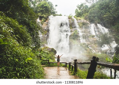 Girl enjoying under Thailand Waterfall in a pure nature environment. Travel enthusiast.