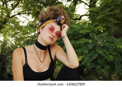 Girl enjoys the day surrounded by nature. Eccentric girl with curly hair takes a selfie. Woman practices yoga.
