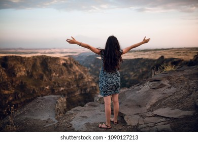A girl enjoys the freedom in the nature. A girl stands with her hands wide open at the edge of the canion in Armenia. Freedom and travel concept