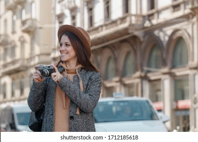 The girl enjoys her weekend and takes pictures of the sights. Against the backdrop of beautiful old, historical buildings
