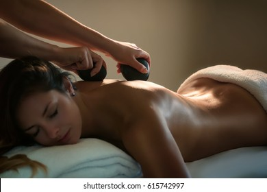 The girl enjoys stone therapy treatment.