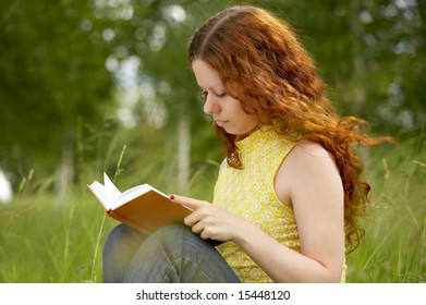 The girl with enthusiasm reads the book in park