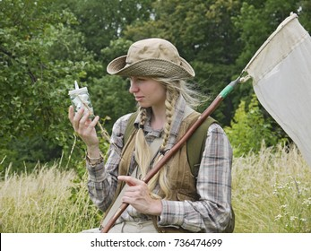A girl entomologist in a field near a forest. Young woman with two plaits, in a hat, dressed in country style holds an insect net and a killing bottle. A student summer field period in the university.