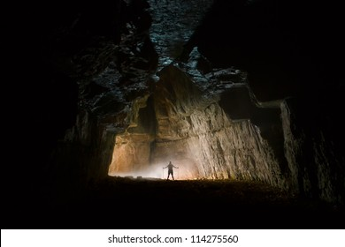 A girl in the entrance of a cave in the Alps, France