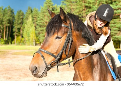 Girl equestrian riding horseback and stroking horse neck. Vibrant summertime horizontal outdoors image.