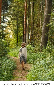 A girl in an ethnic poncho and a hat in a pine forest