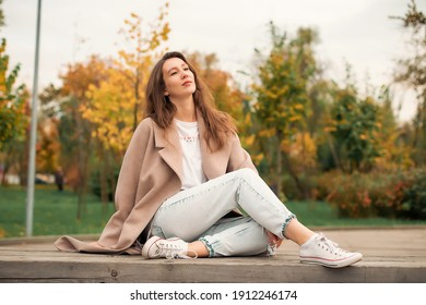 A girl with a Euro-Asian appearance in a pink coat and blue jeans with holes sits on a bench made of gray unpainted boards in a park