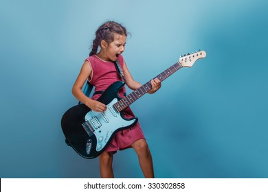 Girl European appearance ten years  playing guitar sings on  a blue  background