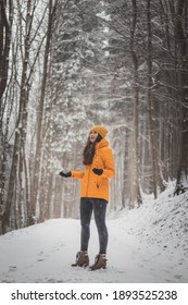 Girl of European descent and aged 20-24 rejoices in the falling snow. A woman stands in the middle of a snowy road in a yellow bold jacket and yellow hats. A real smile.