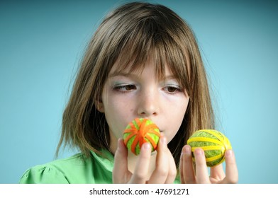 girl evaluating two ornamental eggs