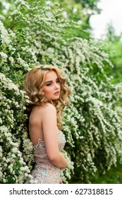 Girl in evening cocktail dress on a spring in the middle among flowering bushes and trees beautiful smiling
