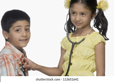 Girl examining a boy with a stethoscope