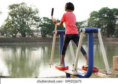 Girl exercise on exercise equipment at local outdoor playground - Thailand