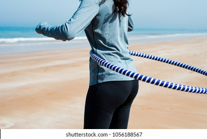 Girl exercising with hula hoop on the beach close up