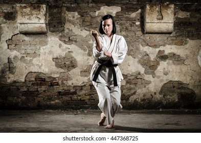Girl exercising karate against old grunge wall. Martial arts.