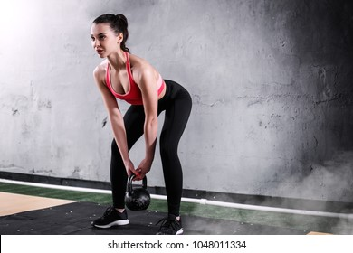 Girl is exercising with a kettle-bell in front of grey concrete wall