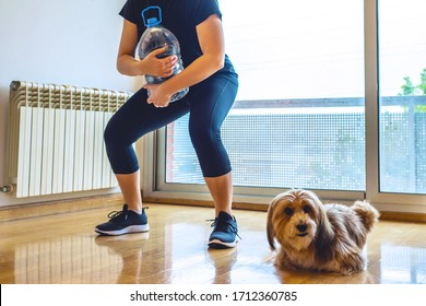 girl exercising lifting five liters water bottle in her home living room with her dog