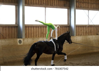 girl is exercising on a black horse