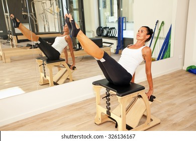 Girl is exercising pilates using pilates chair
