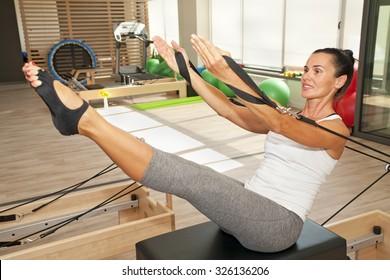 Girl is exercising pilates using pilates device reformer