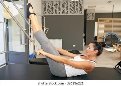 Girl is exercising pilates using pilates device cadillac