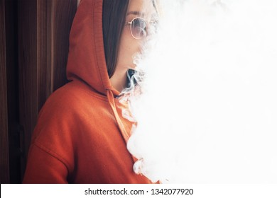 girl exhales a lot of vapor, a white cloud with light space
