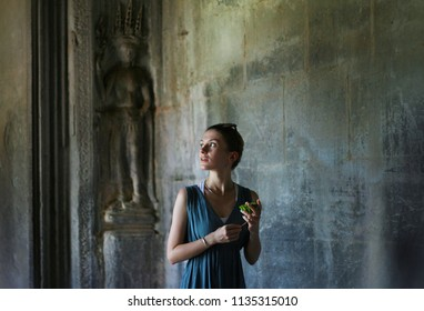 Girl explores mystical ancient temple ruin with lotus flower in hand. South East Asian tourism