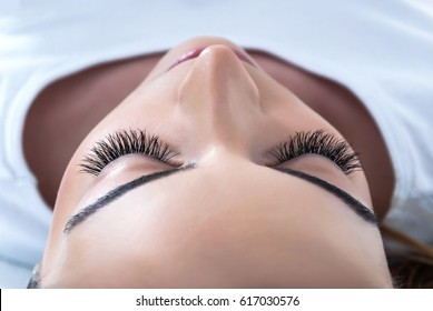 Girl with extended silk eyelashes lies in a beauty studio