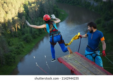 Girl ,extreme athlete, pushes away from the wooden platform during a jump with a rope from a great height, back view, close-up. Ropejumping.