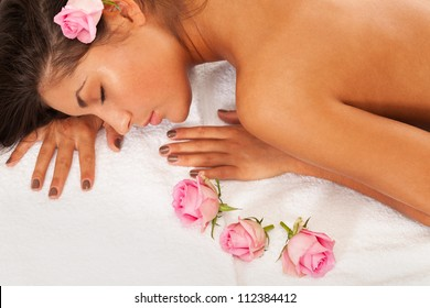 Girl with eyes closed laying on a towel with roses