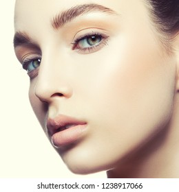 Girl face with natural nude make-up and clean skin over white backgroun. Beautiful Young Woman with Clean Fresh Skin close up. Skincare female health concept