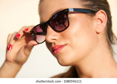 Girl face portrait, with sunglasses, red nail enamel, ponytail, red lipstick