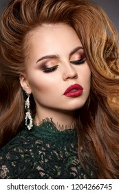 Girl face  with a professional stunning makeup. Red lips, false eyelashes, powder, blush. Volume hairstyle from curls. Chic hair from a young model.