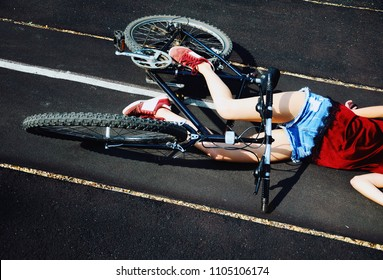 A girl fallen off a bicycle and lying on the road. Accident.