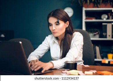 Girl falling asleep while typing on laptop. Sleepy business lady wearing white blouse sitting at office desk working at computer with tape on her eyes.